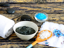 Black healing clay. A salt and black healing clay on a wooden table and stones for massage stock photography