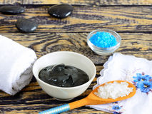Black healing clay. A salt and black healing clay on a wooden table and stones for massage royalty free stock photo