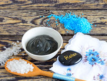 Black healing clay. Sea salt and black healing clay on a wooden table and stones for massage royalty free stock image