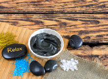 Black healing clay. Sea salt and black healing clay on a wooden table and stones for massage stock photos