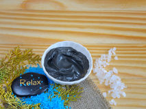Black healing clay. Sea salt and black healing clay on a wooden table and stones for massage stock images