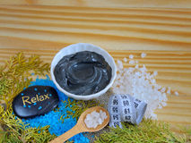 Black healing clay. Sea salt and black healing clay on a wooden table and stones for massage stock photography
