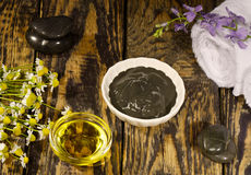Black healing clay for Spa treatments. On the wooden table and massage oil royalty free stock images