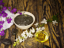 Black healing clay for Spa treatments. On the wooden table and massage oil stock photo