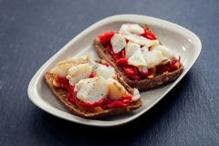 Black healthy bread with cod fish and red pepper on dish stock photo