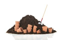 Black heap earth with shovel and flower pots isolated. Black heap sand with shovel isolated on white background stock photography