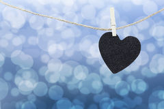 Black Heart hung on hemp rope on abstract colorful bokeh backgro Stock Images
