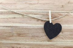 Black Heart hung on hemp rope isolated on wooden background. Stock Photos