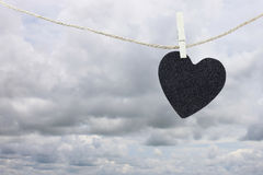 Black Heart paper hanging on a brown hemp rope on rain clouds ba Royalty Free Stock Image
