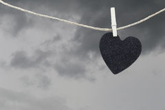 Black Heart paper hanging on a brown hemp rope on rain clouds ba Royalty Free Stock Photography