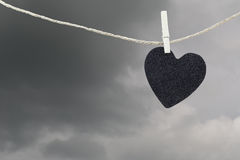 Black Heart paper hanging on a brown hemp rope on rain clouds ba Royalty Free Stock Photos