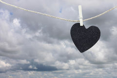Black Heart paper hanging on a brown hemp rope on rain clouds ba Stock Photo