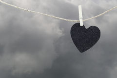 Black Heart paper hanging on a brown hemp rope on rain clouds ba Stock Images