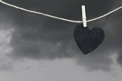 Black Heart paper hanging on a brown hemp rope on rain clouds ba Royalty Free Stock Photo