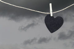 Black Heart paper hanging on a brown hemp rope on rain clouds ba Stock Photos