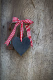 Black heart with a red white checked ribbon hanging on an old do Royalty Free Stock Images