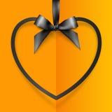 Black heart shape frame hanging on silky ribbon Stock Photos