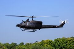 Black Helicopter Flying Above Green Trees Royalty Free Stock Photography