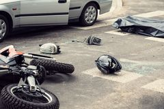 Black helmet and motorcycle on the road after fatal collision wi. Th a car royalty free stock photo