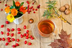 Black herbal tea in a transparent cup on a wooden table. Autumn. Concep stock photography