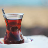 Black herbal turkish tea in traditional glass at the beach Royalty Free Stock Photo