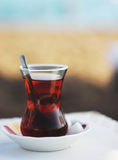 Black herbal turkish tea in traditional glass at the beach Royalty Free Stock Photography