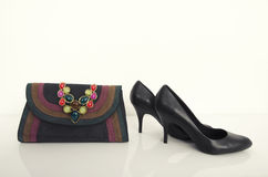 Black high heel woman shoes with an elegant purse and necklace. Royalty Free Stock Photos
