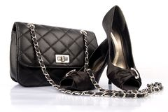 Black high heel women shoes and a bag. On white background royalty free stock image
