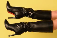 Black high-heeled boots on female feet on a yellow background Royalty Free Stock Images