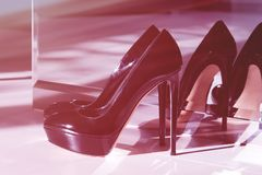 Black high-heeled shoes. Shoes standing near the mirror. A pair of shoes with high heels stock photography
