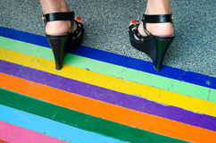 Black high heels standing on the rainbow stripes Stock Image