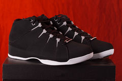 Black high top basketball shoes perched on the box Royalty Free Stock Images