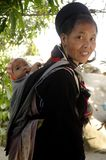 Black Hmong ethnic woman and baby. A Black Hmong woman and her baby. All women carry their baby in the back. They are well all day, despite the hard work the Stock Photos