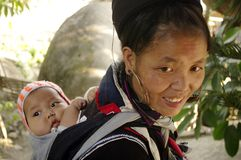 Black Hmong ethnic woman and baby. A Black Hmong woman and her baby. All women carry their baby in the back. They are well all day, despite the hard work the Stock Image