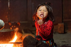 Black Hmong girl making faces. A little girl from the Black Hmong tribe making faces in her home in Sa Pa valley in Vietnam Royalty Free Stock Image