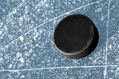 Black hockey puck. On ice rink Royalty Free Stock Photography