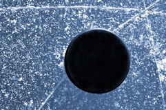 Black hockey puck. On ice rink Stock Images