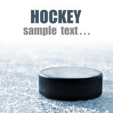 Black hockey puck. On ice rink Royalty Free Stock Images