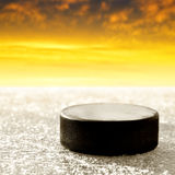 Black hockey puck. On ice rink Stock Image