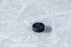 Black hockey puck on ice rink Royalty Free Stock Images