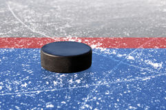Black hockey puck. On ice rink Royalty Free Stock Image