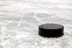 Black hockey puck on ice rink. Black puck on the frozen pond Royalty Free Stock Photo
