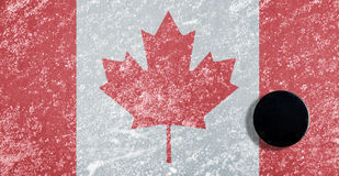 Black hockey puck on ice rink. With Canadian flag Stock Images