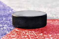 Black hockey puck on ice rink Stock Images