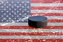 Black hockey puck on ice rink. With flag of the United States Royalty Free Stock Photo