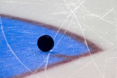 Black hockey puck on ice rink. Winter sport royalty free stock images