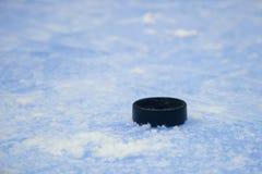Black hockey puck on ice rink. Winter sport stock photo