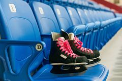 Black hockey skates with ping bootlaces on the chair on the empty stadium. The chairs are blue stock photo