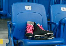 Black hockey skates with ping bootlaces on the chair on the empty stadium. Chair has a number one. Pair of kid`s skates Royalty Free Stock Photos