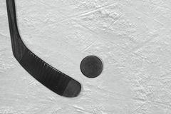 Black hockey stick and puck on the ice. Black stick and puck on the ice hockey rink. Concept, background stock images
